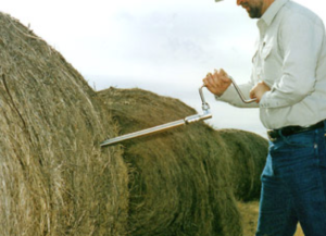 man taking core sample from round bale of hay