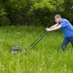 man push mowing tall grass