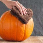 hand washing pumpkin with cloth