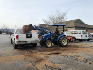 man on tractor loading manure in bed of truck