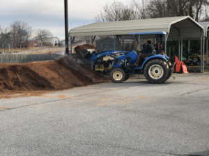 man on a tractor loading compost