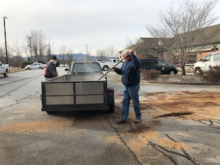 two men putting compost in a trailer
